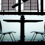 Pictured: A stylized photo of two chairs facing each other from opposite sides of a small table.