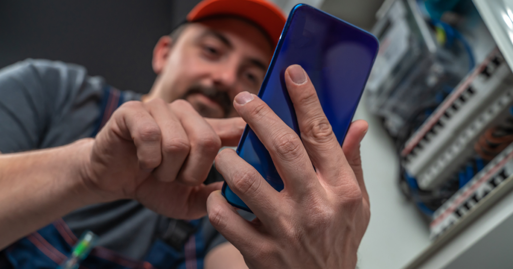 ID: A Caucasian man with a brown mustache uses a blue phone. There is equipment in the background behind him.